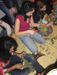 Girls trimming pot on the floor, no buckets or tables